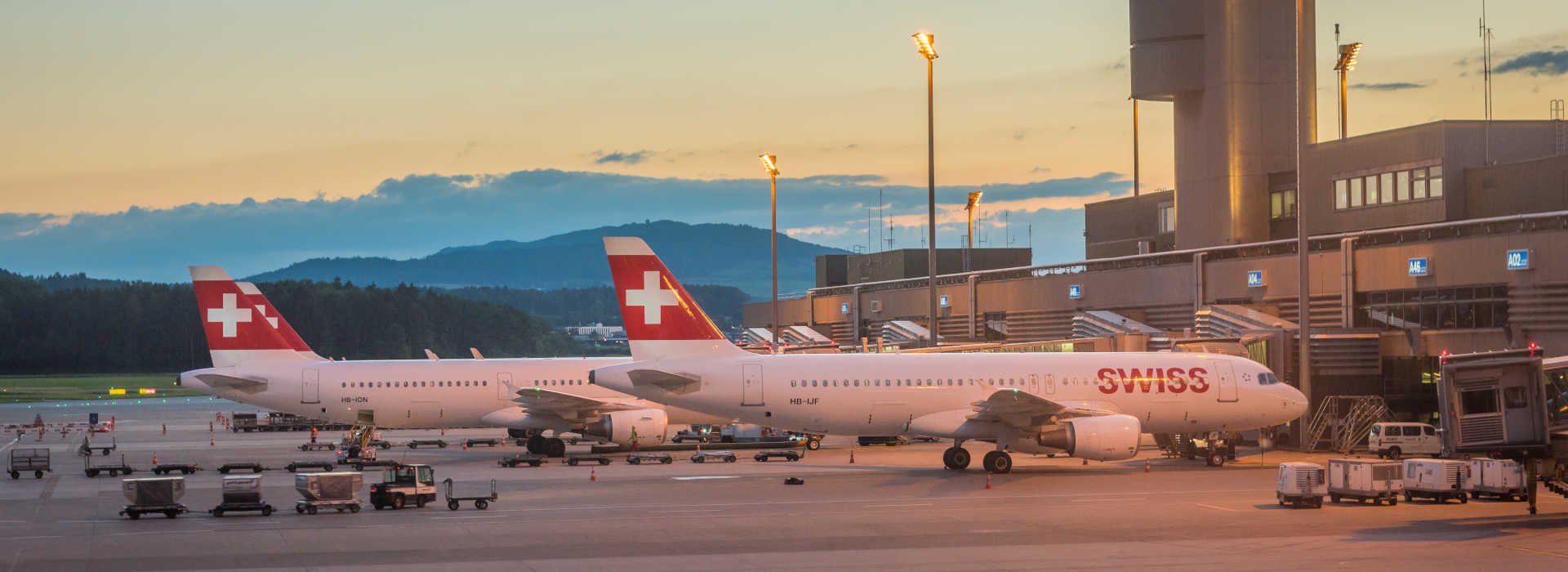 Zurich, Switzerland - July 6, 2016: Kloten airport in Zurich featuring control tower and Swiss International Air Lines aircrafts parked at the gates. The image was taken just after sunset.